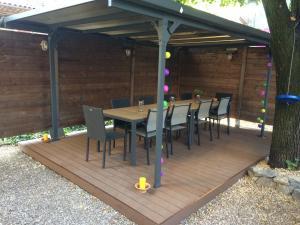 La table d'hôtes sous la pergola et le tilleul  de Côté Jardin Les Vans