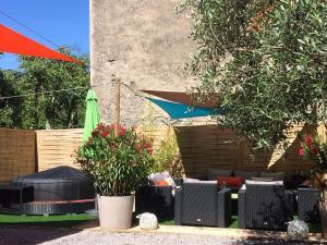 Le jardin avec le  coin salon extérieur et le jacuzzi pour profiter de la douceur ardéchoise